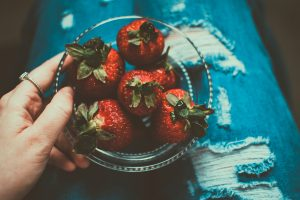 person holding a bowl of strawberries on their lap